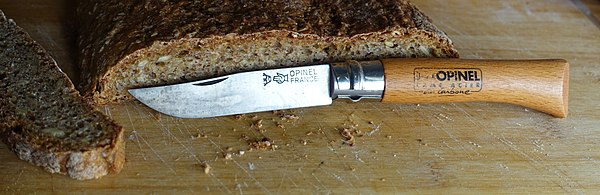 French Opinel pocket/folding knife with bread; showing the typical stains of a carbon steel blade
