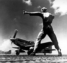 Black and white photograph of a man wearing military uniform facing a World War II-era single-engined fighter while gesturing to his left