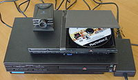 Comparison of the Slimline PlayStation 2 design with the PlayStation 2, with an Eye Toy on top.