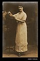 Photographic postcard of a woman dressed in white leaning on a high table (10279281595).jpg