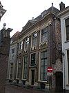 foto van Huis met pilastergevel ter breedte van vier venstervakken en voorzien van middenrisaliet en zijlisenen