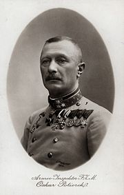 A male with a moustache wearing medals and a military uniform.
