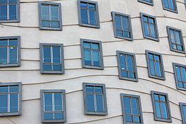 Vue sur la façade de béton d'un immeuble et ses nombreuses fenêtres en décalage les unes des autres et reliées aléatoirement, d'étages en étages, par des lignes courbes.