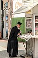Priest buying newspaper (15326539258).jpg