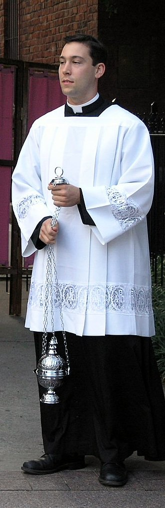 Surplice - Seminarian vested in a pleated Roman-style surplice with lace inserts, holding a thurible.