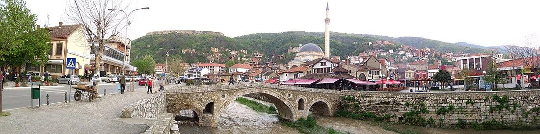 Altından Akdere'nin aktığı tarihî Taşköprü, Sinan Paşa Camii, sol üstte Prizren Kalesi, resmin sağında da Şadırvan ile Prizren şehri