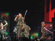 Image shows a performance onstage where the performers are wearing military garments. Central to them is a blond woman, who carries a rifle in her left hand while singing into a microphone.