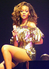A young brunette woman sitting on a piano. She wears a golden dress and holds a microphone in her right hand