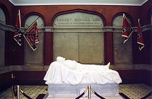 "Lee Chapel - ""Recumbent Statue"" of Robert E. Lee asleep on the battlefield, by Edward Valentine. Located in the Lee Chapel in Lexington, Virginia, it is often mistakenly thought to be a tomb or sarcophagus, but Lee is actually buried beneath the chapel. In the summer of 2014, the replica Confederate flags pictured in this photo were removed from the chapel after student protests."
