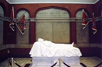 """Lee Chapel - """"Recumbent Statue"""" of Robert E. Lee asleep on the battlefield, by Edward Valentine. Located in the Lee Chapel in Lexington, Virginia, it is often mistakenly thought to be a tomb or sarcophagus, but Lee is actually buried beneath the chapel. In the summer of 2014, the replica Confederate flags pictured in this photo were removed from the chapel after student protests."""