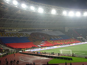 "Sport in Russia - Russian football fans with a gigantic ""Go Russia!"" banner, featuring the Russian Bear on the background of the Russian flag"