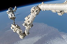 An astronaut, dressed in a white spacesuit, attached to the end of a long, jointed robotic arm covered in white insulation. The Earth's horizon and the blackness of space serves as a backdrop.