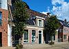 foto van Groot dorpshuis met omlijste ingang en zesruitsvensters onder twee evenwijdige zadeldaken tussen topgevels met hoekschoorstenen