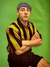 Man in football kit and beret, with his arms crossed