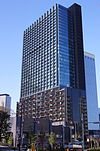 Ground-level view of a blue and black, rectangular, glass high-rise; one facade is covered in slightly protruding vertical stripes.