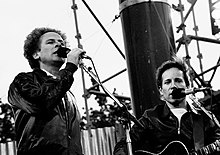 Two men singing into microphones, in a low-angle close-up, black-and-white