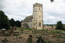 A stone church seen from the northwest.  The tower is battlemented, and the relatively small plain body of the church extends beyond it