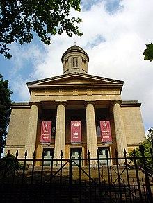 The entrance face of a church in Neoclassical style, with four columns supporting a pediment, over which is a cupola.