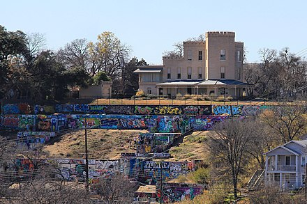 The HOPE Outdoor Gallery, overlooked by the historic Texas Military Academy building, the oldest standing educational building in Texas TMI castle austin 2014.jpg