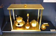 A photograph of several golden vessels, drinking cups, a guilted ladle and instruments, are displayed on a stand. Beside the stand is a golden plate and cup on a golden saucer