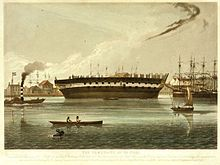 Print of the hull of a sailing ship without masts or rigging aground on mud beside a river.