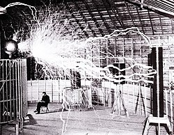 "Publicity picture of a participant sitting in his laboratory in Colorado Springs with his ""Magnifying Transmitter"" generating millions of volts. The arcs are about 7 meters (23 ft) long. (Tesla's notes identify this as a multiple exposure.)"