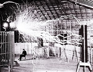 "Publicity picture of a participant sitting in his laboratory in Colorado Springs with his ""Magnifying Transmitter"" generating millions of volts. The arcs are about 7 meters (23 ft) long. (Tesla's notes identify this as a double exposure.)"