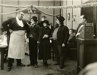 The Immigrant (1917 film) - The huge waiter (played by Eric Campbell) glowers at the immigrant (Charlie Chaplin). To his right are Edna Purviance playing another immigrant and Henry Bergman as a bearded artist.