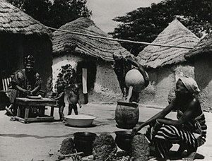 Housewife - A housewife in Yendi, Kumasi, Ghana, pours water into a meal and her children play; 1957