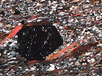 Metamorphism - A cross-polarized thin section image of a Garnet-Mica-Schist from Salangen, Norway showing the strong strain fabric of schists. The black (isotropic) crystal is garnet, the pink-orange-yellow (commonly referred to as high order) colored strands are muscovite mica, with the brown crystals are biotite mica. The grey and white (low first-order) crystals are quartz and (limited) feldspar.