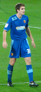 A man wearing blue shirt and shorts with sky blue trim, standing on a grass field.