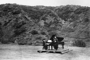 Hollywood Bowl - Two women performing on a barn door in the first known musical event at the Hollywood Bowl, ca.1920.  According to an article in the San Diego Union newspaper, June 19, 1941, the woman at the piano was Carrie Jacobs-Bond, one of the originators of the Theatre Arts Alliance and a resident of nearby Hollywood Heights.  She was assisting in testing the acoustics.  The barn door was placed approximately where the band shell was built.