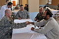 U.S. Army Capt. Jeremy Spruce, of Headquarters and Headquarters Company commander, 1st Special Troops Battalion, Task Force Spartan, shakes hands with Malik Nimat, from the District Development Authority, during 100821-A-RN448-045.jpg