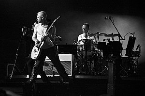 Larry Mullen Jr. - Mullen (right) performing with U2 in 2009