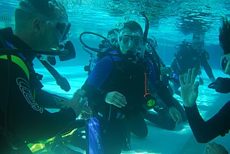 Diving instructor - Instructor and learner divers practicing scuba skills in confined water