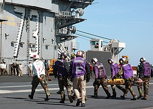 USS George Washington (CVN-73) - Washington personnel carry injured personnel across the ship's flight deck after four personnel were rescued from the burning merchant fishing vessel, Diamond Shoal.