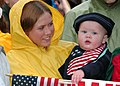 US Navy 030523-N-3642E-007 A Navy wife and mother holds her nine-month-old child, while waiting in the pouring rain for her husband to arrive home from a six-month deployment aboard USS Harry S. Truman (CVN 75).jpg
