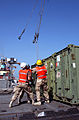 US Navy 040227-N-0743B-021 Members assigned to Naval Expeditionary Logistics Support Force Forward Alpha, move cables into place to attach to cargo containers being off-loaded from the Military Sealift Command (MSC) fast sealif.jpg