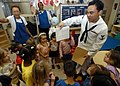 US Navy 050209-N-3019M-002 Dental Technician 3rd Class Chris Mar hands out dental information sheets to children at the Child Development Center on board Naval Station Pearl Harbor, Hawaii.jpg