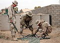 US Navy 050213-N-0577F-003 Electrician's Mate 3rd Class Stewart Adams, right, assigned to Naval Mobile Construction Battalion Four (NMCB-4), Task Force Echo, conducts an inventory of an OE-254 antennae bag.jpg