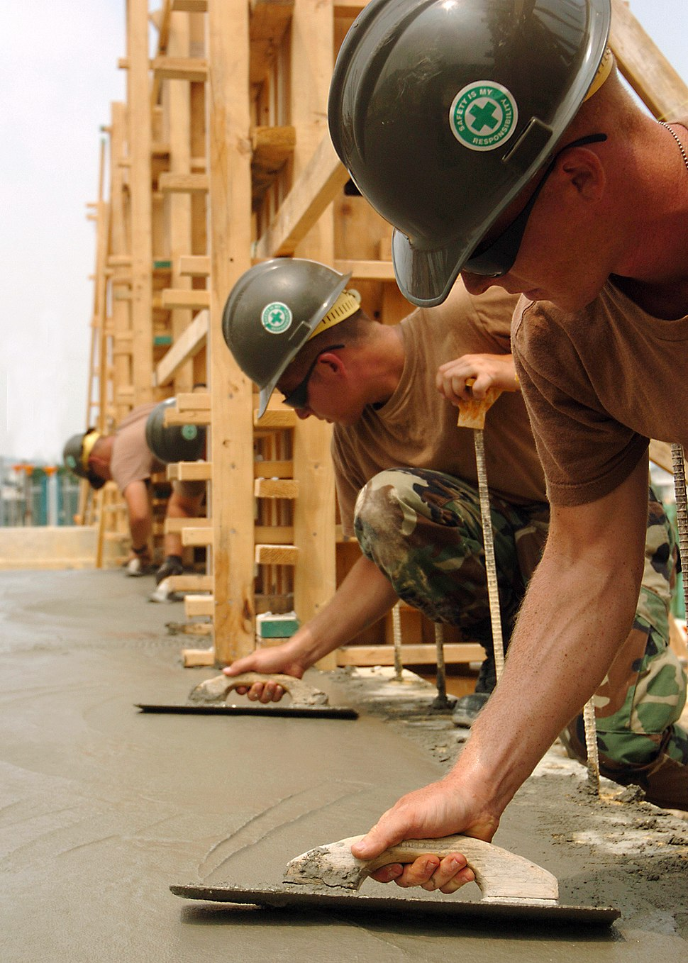 US Navy 050705-N-1261P-025 Builder Constructionman Guthrie Kees and Utilitiesman 3rd Class Robert Jones use trowels to smooth freshly poured concrete for a new dispatch office