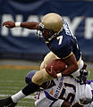 US Navy 060902-N-9693M-001 U.S. Naval Academy Midshipman slot back Reggie Campbell is tackled by East Carolina Pirates linebacker Fred Wilson in the first half of play at Navy - Marine Corps Memorial Stadium.jpg
