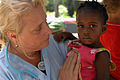 US Navy 071005-N-7088A-130 Genie Lindsey, a Project Hope registered nurse attached to Military Sealift Command hospital ship USNS Comfort (T-AH 20), holds a little girl visiting the Onverwacht Clinic.jpg