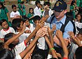 US Navy 071016-N-6710M-004 Information Systems Technician Seaman Drew T. Spaeth hands out candy to the students of Gordon Heights Elementary School while conducting a community relations project in the Republic of Philippines.jpg