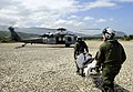 US Navy 100125-N-5345W-138 Air crewmen assigned to the Sea Knights of Helicopter Sea Combat Squadron (HSC) 22 prepare to load an injured Haitian man onto an MH-60S Sea Hawk helicopter.jpg