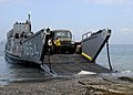 US Navy 100126-N-5244H-001 Seabees off-load heavy equipment from a landing craft unit on the shore of Bonel.jpg