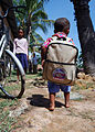 US Navy 100610-N-8539M-278 A Cambodian boy walks away with a backpack of hygiene items after visiting a U.S. Navy dentist during a Cooperation Afloat Readiness and Training (CARAT) Cambodia 2010.jpg