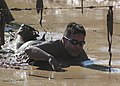 US Navy 111030-N-QF596-023 Petty Officer 1st Class Darryl Hill crawls through the mud pit, the final obstacle at the Warrior Dash in Hollister, Cal.jpg