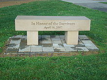 "Bench engraved with ""In Honor of the Survivors"" and ""April 16, 2007"" standing on an area of pavement blocks surrounded by grass."
