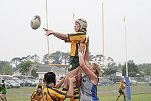A female player in yellow and green kit and wearing a white scrum cap, jumps to collect a ball while supported by teammates.